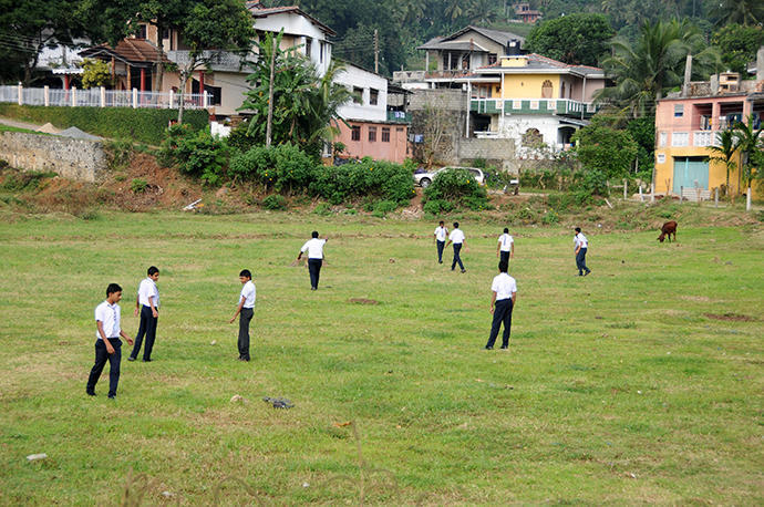 Children playing soccer in their school uniforms-probably their sports lesson